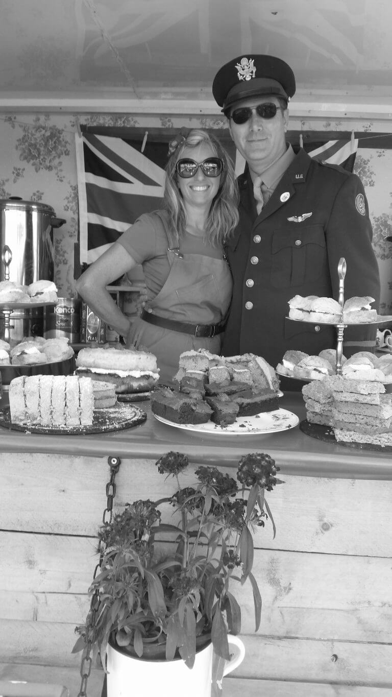 Landgirl with pilot serving cakes and tea at Outside Catering Event